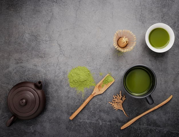 Top view of matcha tea with wooden scoop and teapot