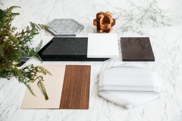 Top view of material selections including granite tile, marble tile, acoustic tile, walnut and ash wood laminate with plant on marble top table.