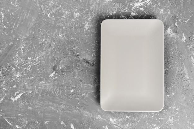 Top view of matte rectangular empty plate on dark background
