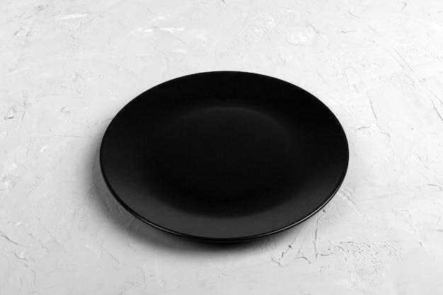 Top view of matte round empty black plate on dark cement