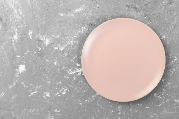 Top view of matte round empty pink dish on dark cement background space for you design