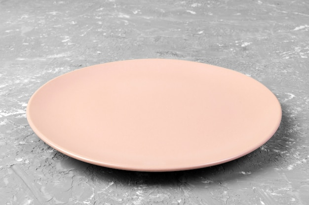 Top view of matte round empty rose plate on grey cement