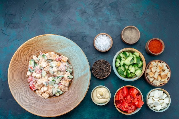 Вид сверху овощной салат с майонезом и свежие нарезанные овощи на темно-синем столе салат еда обед