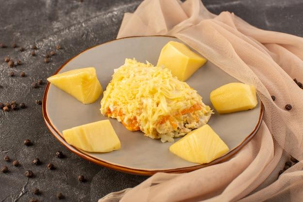 Un'insalata di verdure mayyonaised di vista superiore con il pollo dentro e il formaggio fresco dentro il piatto sul piatto grigio del pasto dell'alimento dell'insalata dello scrittorio