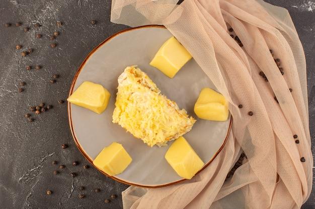 Un'insalata di verdure mayyonaised vista dall'alto con pollo all'interno e formaggio fresco all'interno del piatto con semi di caffè sul pasto di cibo insalata di scrivania grigia