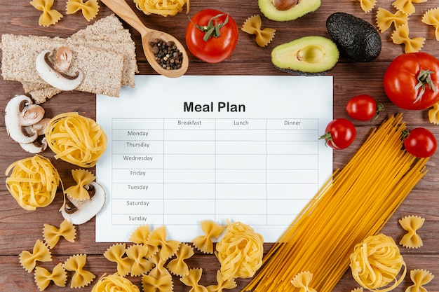 Top view of meal plan with pasta and avocado