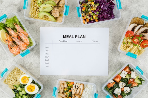 Top view of meals in casseroles with plan and salads