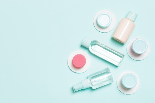 Top view of means for face care: bottles and jars of tonic, micellar cleansing water, cream, cotton pads on blue surface