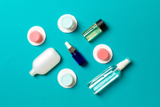 Top view of means for face care: bottles and jars of tonic, micellar cleansing water, cream, cotton pads on colored background. bodycare concept with empty cpace for your ideas.