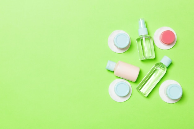 Top view of means for face care: bottles and jars of tonic, micellar cleansing water, cream, cotton pads on green. flat lay composition with copyspace