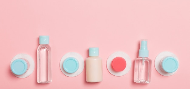 Top view of means for face care: bottles and jars of tonic, micellar cleansing water, cream, cotton pads on pink background. bodycare concept with empty cpace for your ideas