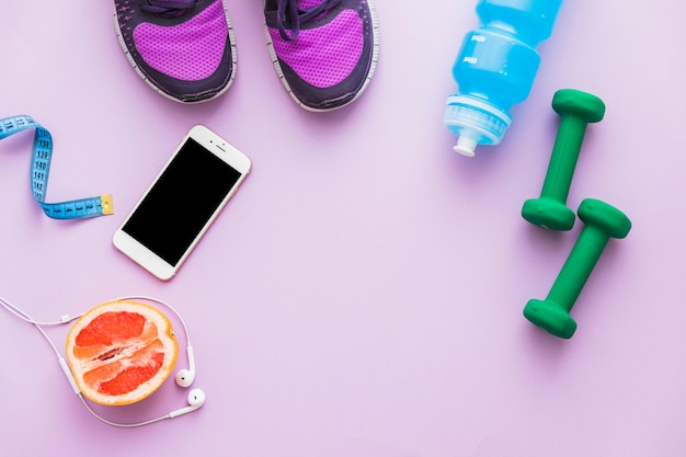 Top view of measuring tape; dumbbell; shoes; halved orange fruit; water bottle; cellphone and earphone on pink backdrop