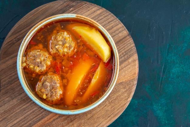 Вид сверху суп из фрикаделек с картофелем внутри круглой тарелки на темно-синей поверхности