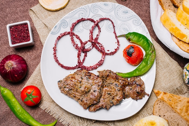 Top view meat basturma kebab with tomato and hot pepper on the grill with onion in sumac