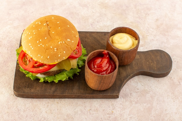 A top view meat burger with cheese and green salad along with ketchup and mustard