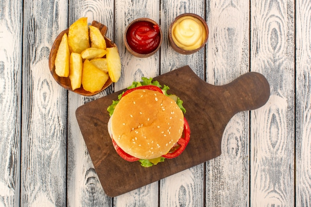 A top view meat burger with cheese and green salad potatoes and dips