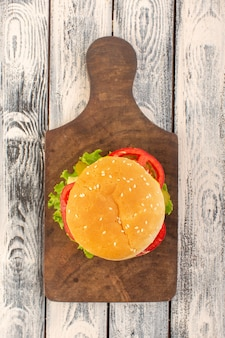 A top view meat burger with cheese and green salad