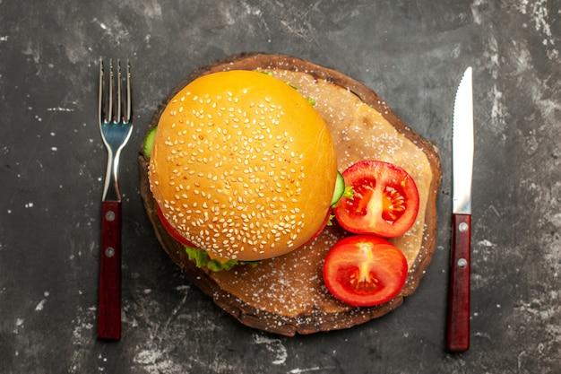 暗い表面のパンのファーストフードサンドイッチに野菜とチーズを添えたトップビューミートバーガー