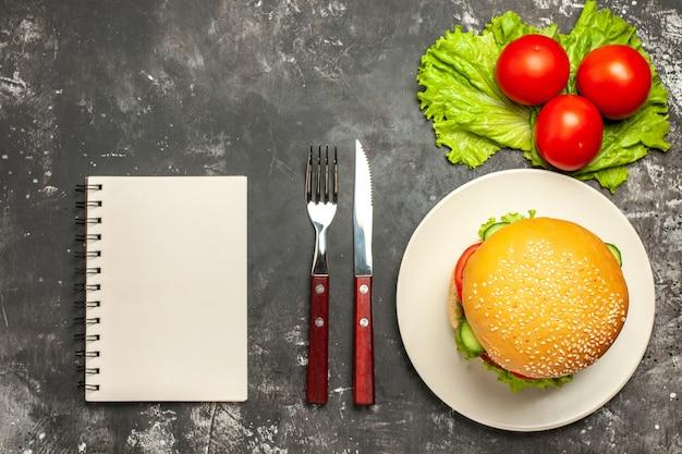 暗い表面のパンサンドイッチファーストフードに野菜とサラダを添えたトップビューミートバーガー