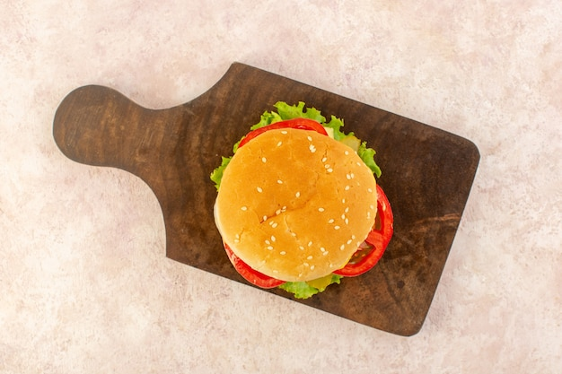 A top view meat burger with vegetables cheese and green salad