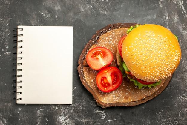 暗い表面のパンファーストフードサンドイッチに野菜とトップビューミートバーガー