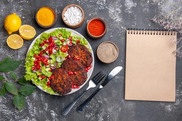 Вид сверху мясные котлеты со свежим салатом и приправами