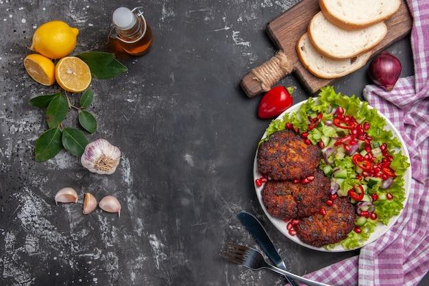 Cotolette di carne vista dall'alto con insalata e pane