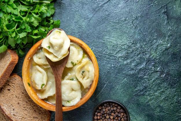 Gnocchi di carne vista dall'alto all'interno del piatto di legno con verdure e pagnotte di pane sulla superficie blu scuro