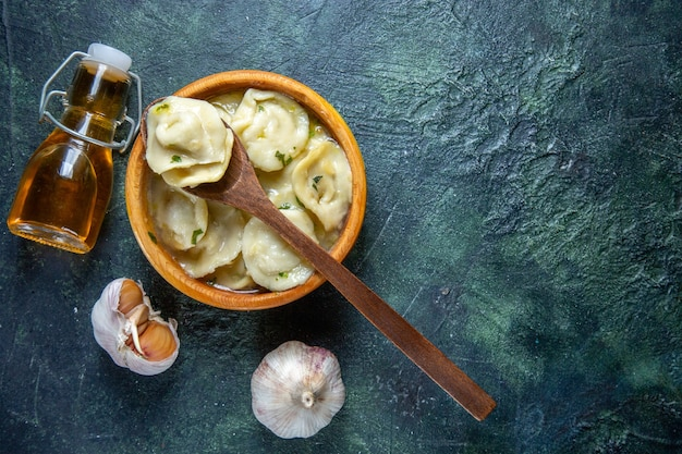 Top view meat dumplings inside wooden plate with oil onion and garlic on dark surface