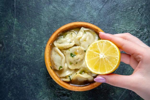 暗い表面にレモンスライスを保持している女性と上面図肉餃子