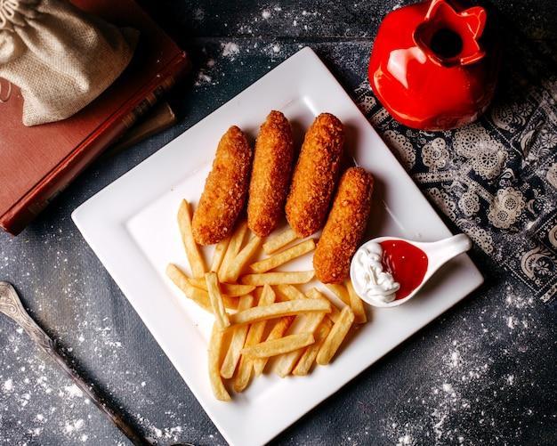 Vista dall'alto patatine fritte con patatine fritte all'interno del piatto bianco e con ketchup e maionese sul pavimento grigio