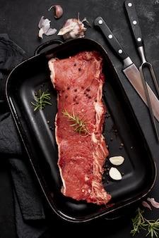 Вид сверху мясо в тарелке со столовыми приборами