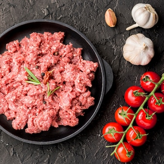 Top view of meat on plate with garlic and tomatoes
