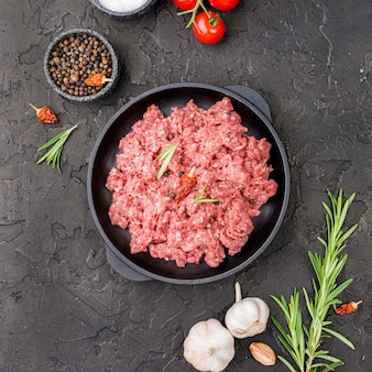 Top view of meat on plate with tomatoes and herbs