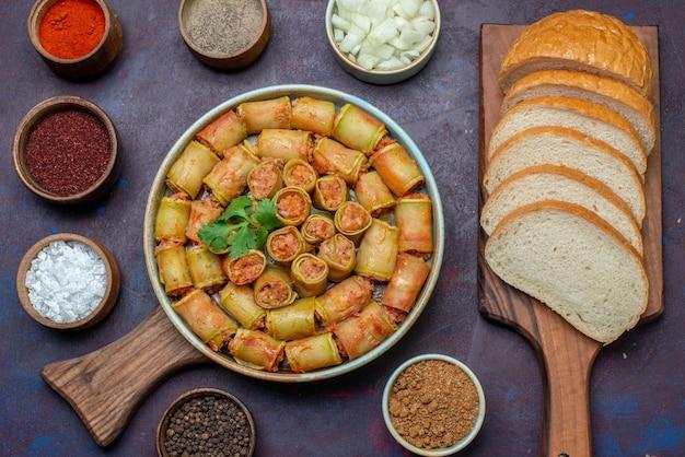 Вид сверху мясные рулеты, скрученные в тыквах внутри сковороды вместе с приправами и хлебом на темном столе, мясо, овощная еда, ужин