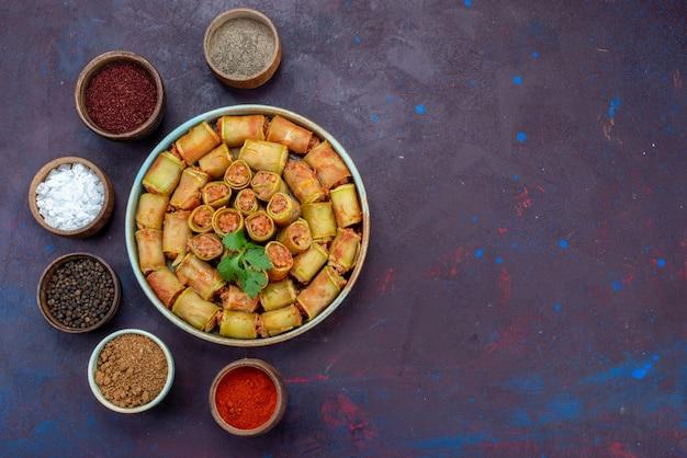 Vista dall'alto involtini di carne arrotolati all'interno di zucche insieme a condimenti sulla cena di verdure farina di carne cibo scrivania scuro