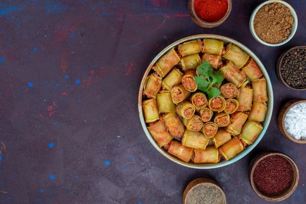 Vista dall'alto involtini di carne arrotolati all'interno di zucche con condimenti sulla scrivania scura cibo carne pasto cena vegetale