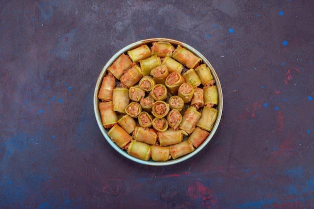 暗い背景の鍋の中で野菜と一緒に巻かれた上面図の肉ロール肉夕食食品食事野菜
