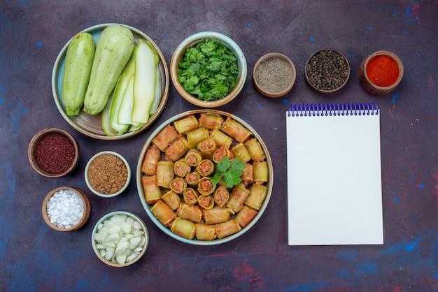 Vista dall'alto involtini di carne arrotolati con verdure all'interno della padella con condimenti di verdure sulla scrivania scura carne cena cibo vegetale pasto