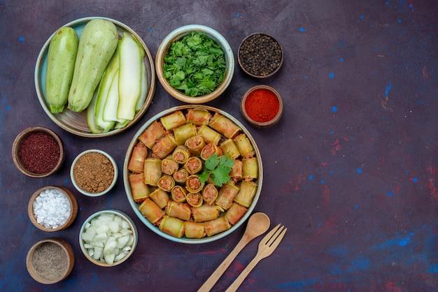 Vista dall'alto involtini di carne arrotolati con verdure all'interno della padella con condimenti di verdure sulla scrivania scura carne cena cibo vegetale