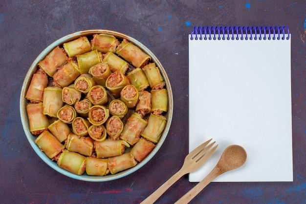 暗い背景にメモ帳付きの鍋の中に野菜を巻いた上面図肉ディナー食品野菜ミール