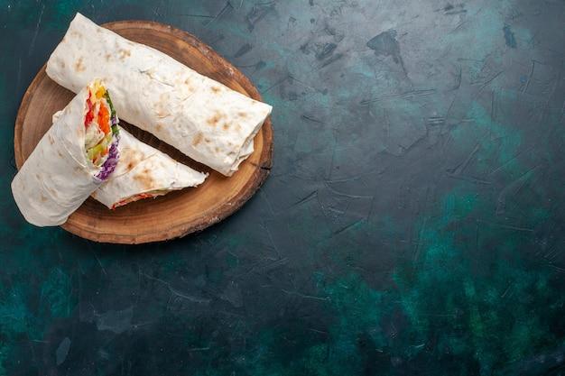 トップビューミートサンドイッチ紺色のデスクに野菜を添えて串焼きにした肉で作ったサンドイッチサンドイッチハンバーガーフードミールランチミート写真