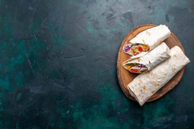 Vista dall'alto sandwich di carne un panino a base di carne alla griglia allo spiedo affettato sulla scrivania blu scuro panino hamburger cibo pasto pranzo carne foto
