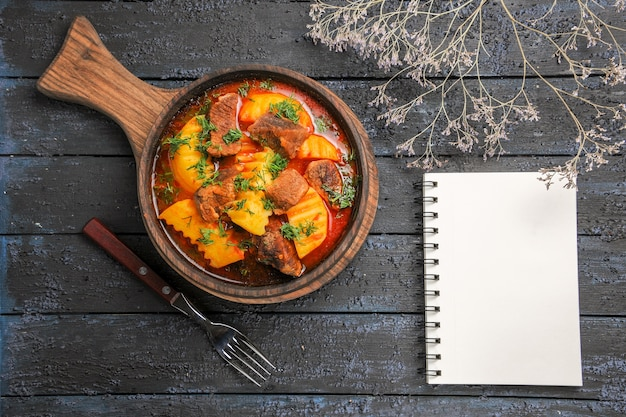 어두운 책상에 채소와 감자가 들어간 상위 뷰 고기 소스 수프