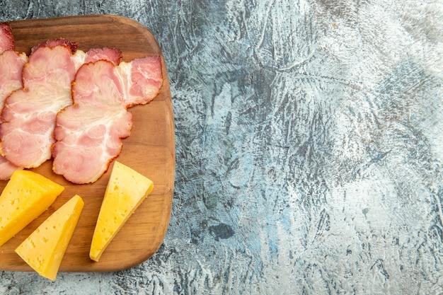 회색 배경에 도마에 있는 상위 뷰 고기 조각 치즈 조각