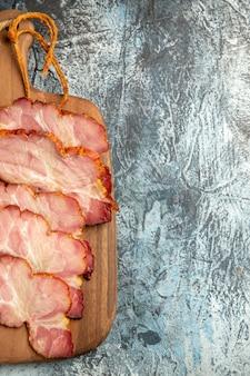 Fette di carne vista dall'alto sul tagliere su superficie grigia