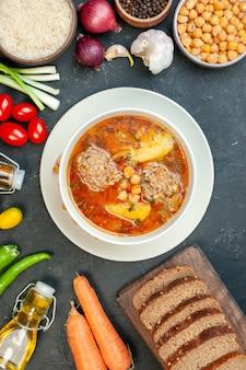 Zuppa di carne vista dall'alto con pagnotte di pane e condimenti su sfondo scuro