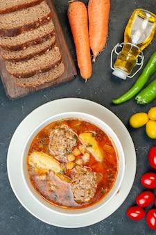Zuppa di carne vista dall'alto con pagnotte di pane e condimenti su sfondo grigio scuro