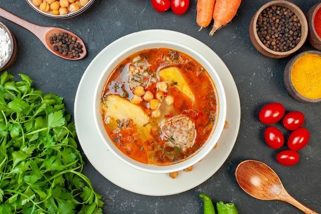 Zuppa di carne vista dall'alto con verdure e condimenti su sfondo scuro