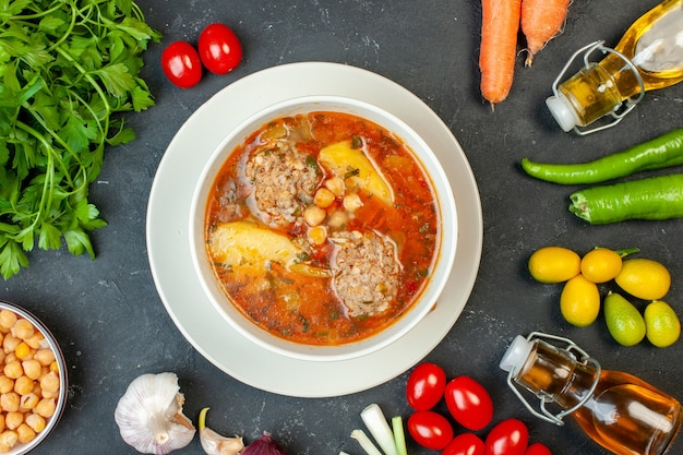 Zuppa di carne vista dall'alto con verdure e verdure su sfondo grigio scuro